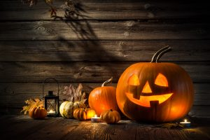 Different sizes of pumpkins and a jack-o-lantern against wooden background.
